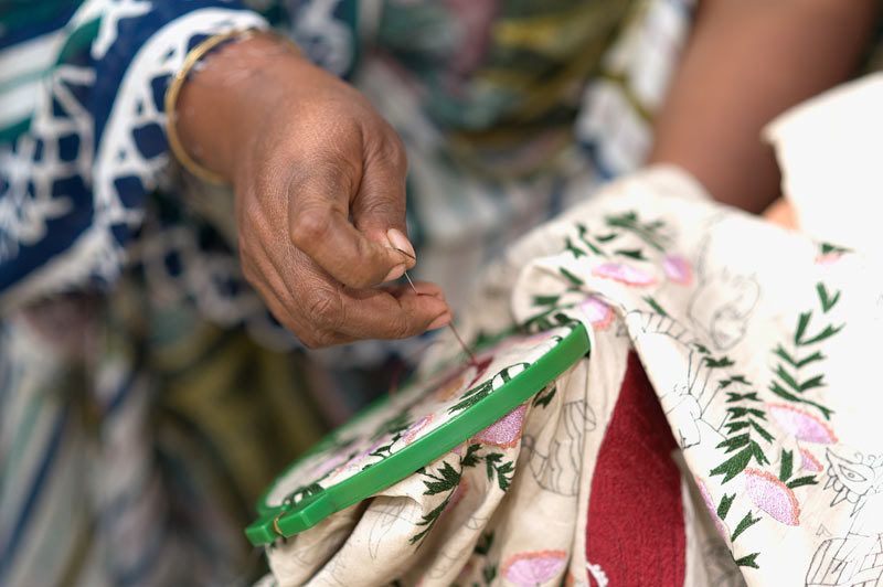 Focus on a woman's hand embroidering a colourful cloth using a contemporary skill of nakshi kantha.