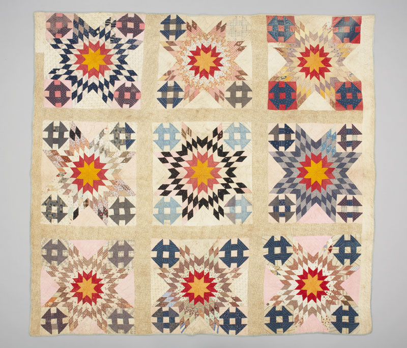 A rectangular nine squared quilt, combining patterns of stylized red and yellow stars with a traditional 'Hole in the Barn Door' pattern.