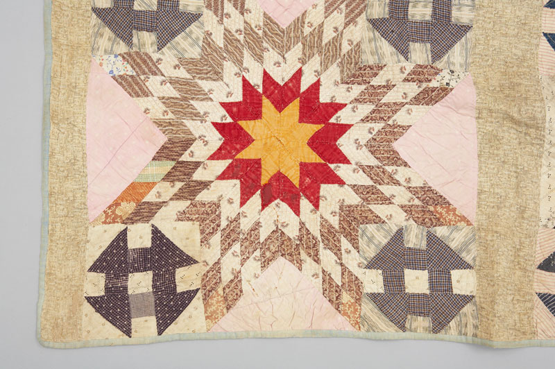 Detail showing one of nine quilt squares, showing a pattern of stylized geometric red and yellow stars.