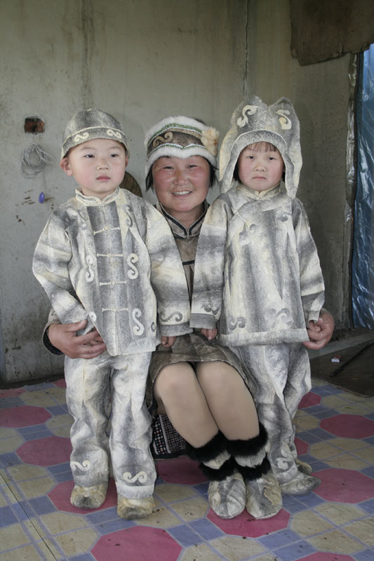 Creator of the coat, You Wenfeng, crouches to pose with her grandsons in matching salmon skin outfits, China, 2006.