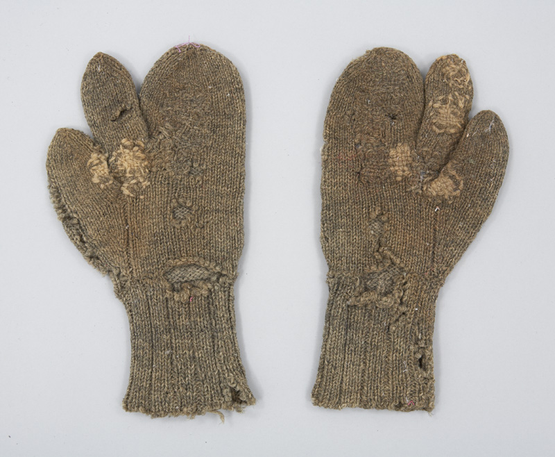 Rear view of roughly woven grey wool mittens with separate index finger, designed for fisherman to grip lines while keeping their hands warm.