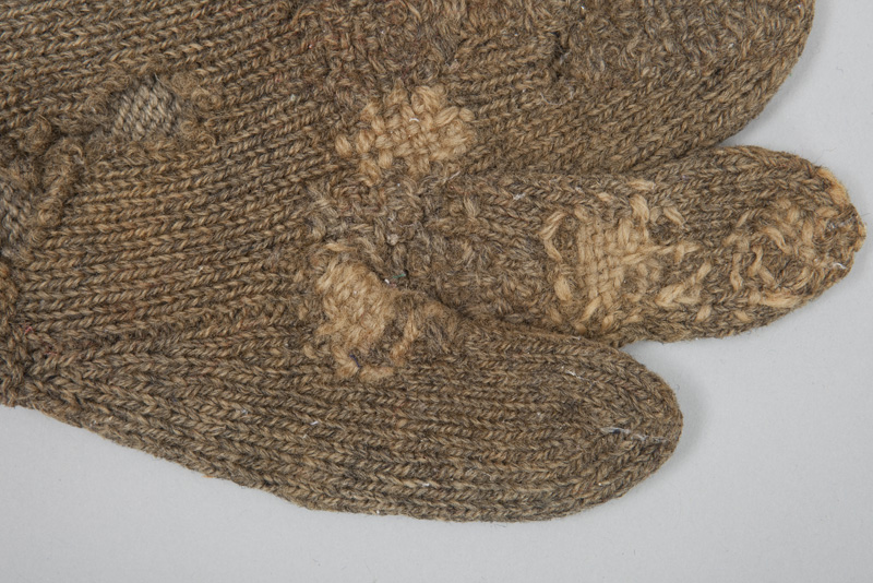Detail view of repair work on roughly woven grey wool mittens, designed for fisherman to grip lines while keeping their hands warm.