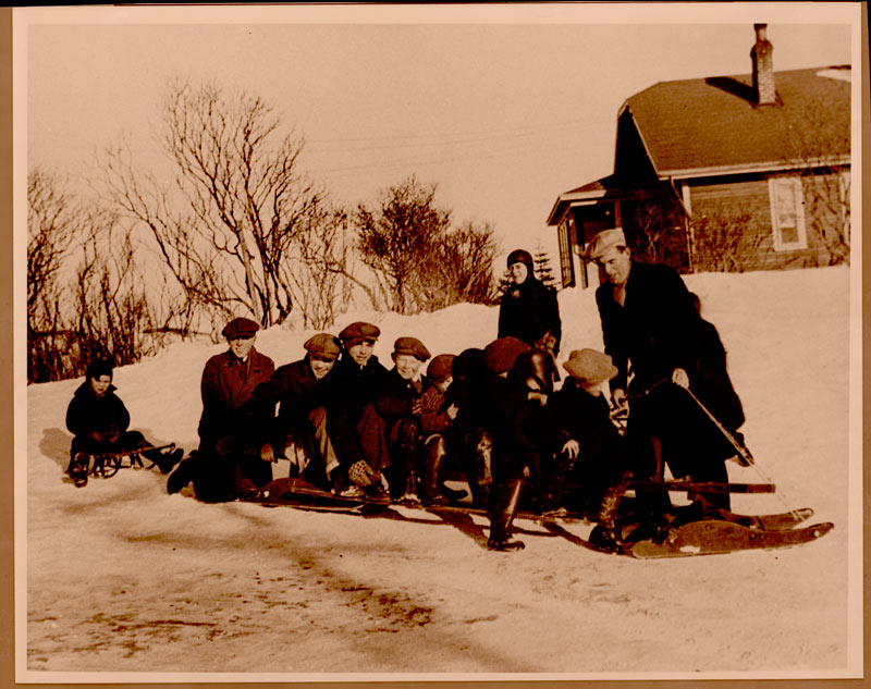A dozen young boys crowd on and around a long wooden snow sled in winter, Newfoundland, 1942.