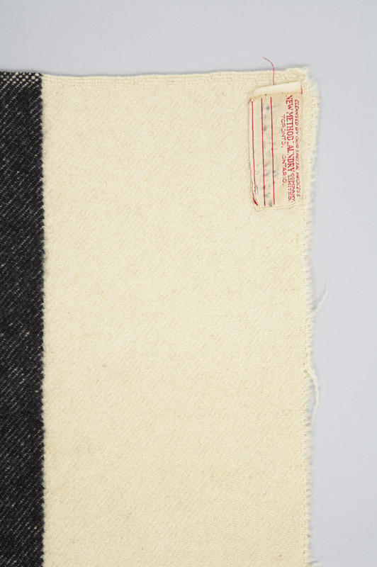 Tag for a white rectangular woven wool blanket indicating it is from the Hudson's Bay Company.