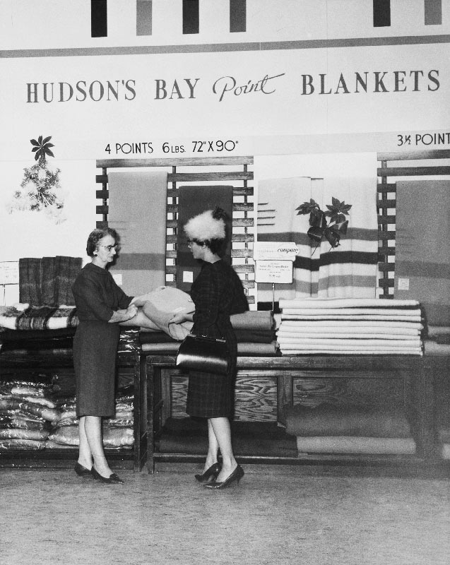 Two woman stand in front of a large blanket display at the Hudson's Bay Company, Winnipeg, Manitoba, 1963.