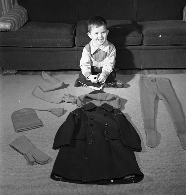 A young boy seated on floor of home with life size pieces that inspired the doll clothing, 1952.