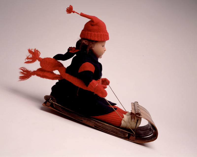 A doll on a wooden sled outfit made of dark blue wool and red wool for the toque, mittens, scarf and pants.