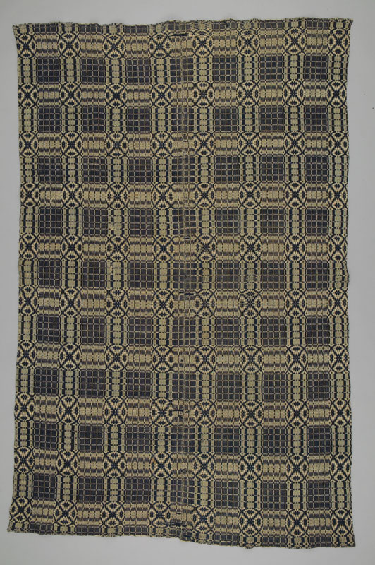 A blue and beige wool coverlet made with a 'Chariot Wheel' and 'Church Windows' pattern made in New Brunswick.