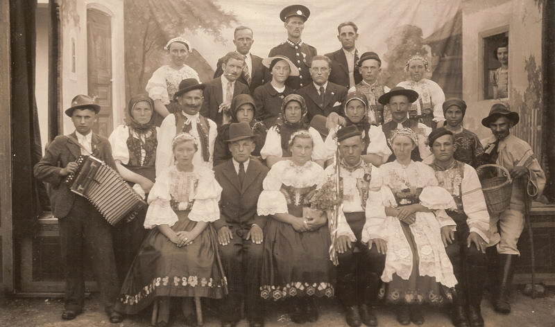 Men and women pose for a group photo in Špačince wearing traditional folk costumes on a local stage.