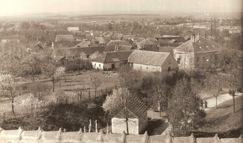 Historic aerial view of the town of Špačince, near Trnava in Slovakia, with tightly packed wooden houses in foreground.