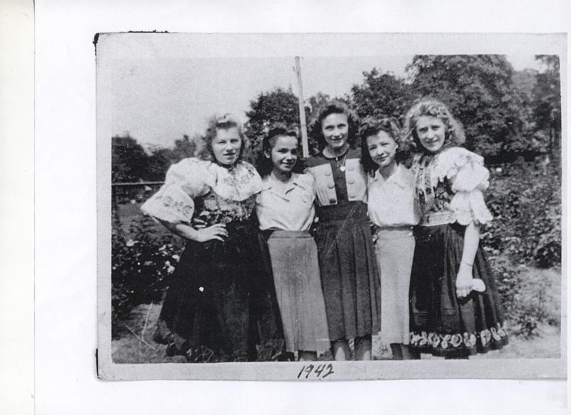 A group of girls stand posing in an embrace, including Anne Fundarek wearing this traditional costume, 1942.