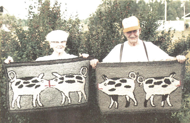 An elderly man and woman hold up their hooked rug artworks depicting local livestock in Gagetown, New Brunswick.