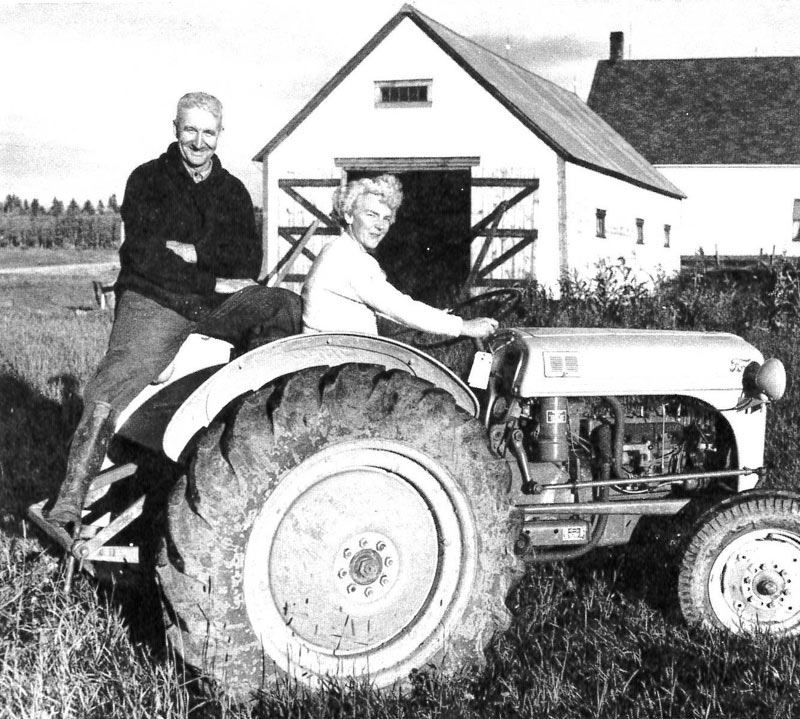 Rug hookers Lydia and Raymond Scott pose on back of tractor in Summer Hill, New Brunswick, 1952.