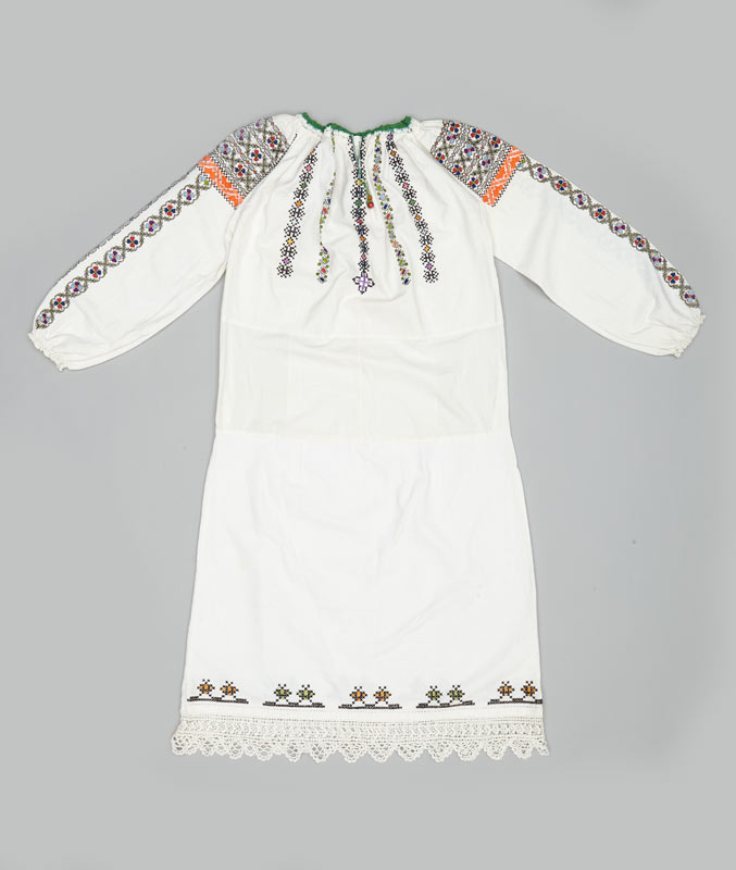 A white embroidered blouse, part of a traditional festive wedding costume in Romania.