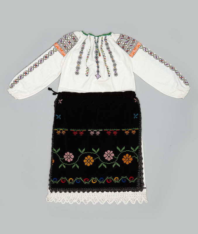 A white embroidered blouse with a black floral embroidered skirt comprises a traditional festive wedding costume in Romania.
