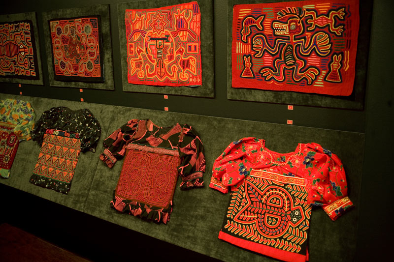 Several different vividly coloured blouse panels known as molas on display at the Textile Museum of Canada.