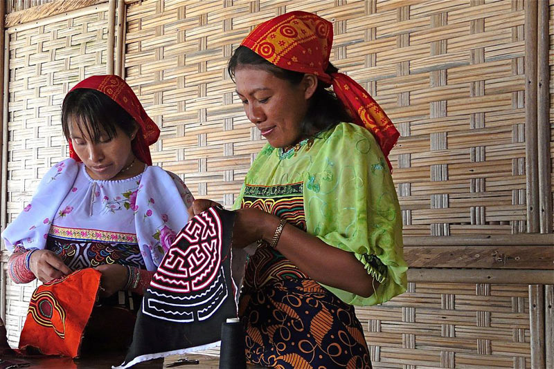 Two women stand in a hut in traditional Panamanian dress sewing molas on the San Blas Islands, Panama.