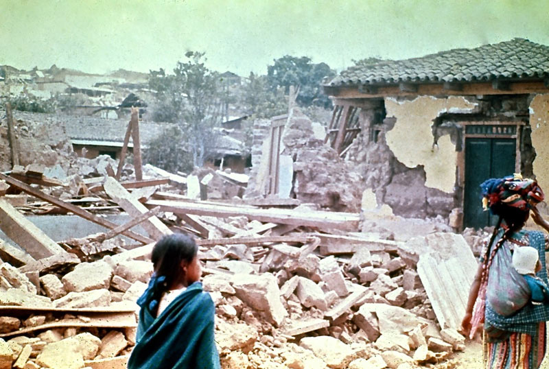 Two young girls walk in front of a building destroyed by earthquake in the village of San Andrés Itzapa, 1976.