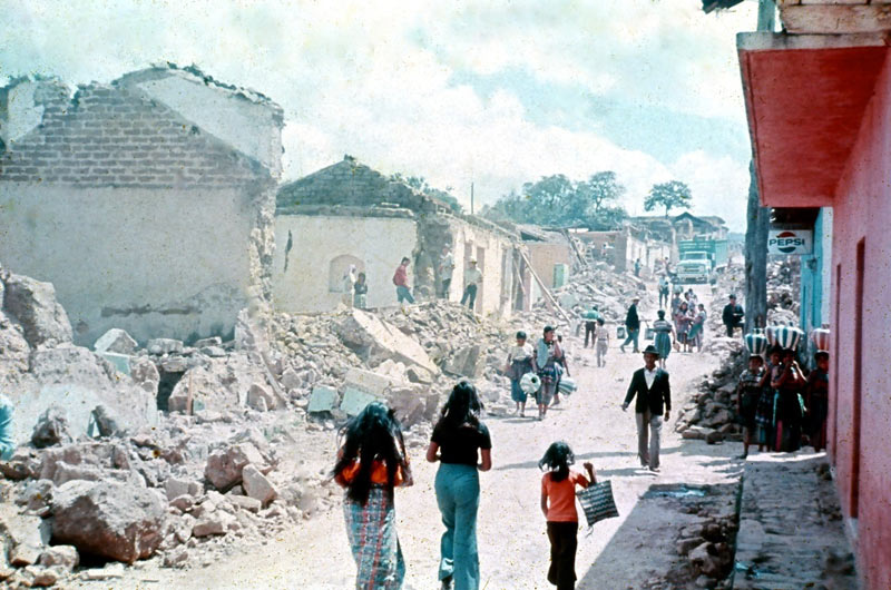 A number of people walking down a rubble-lined street after an earthquake in San Andrés Itzapa, 1976.