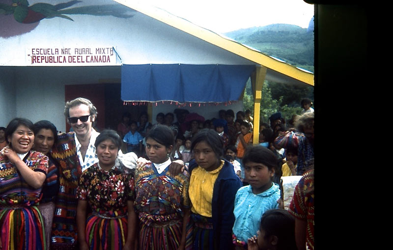 A man stands posing with a large crowd of women in traditional Guatemalan dress, 1977.