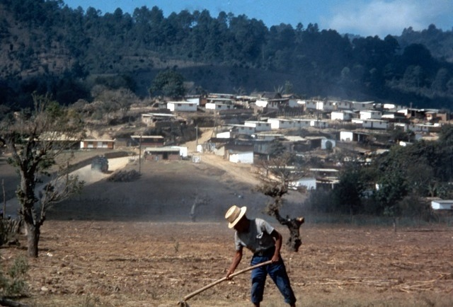 A local man works in a field in front of the small Guatemalan village of San Andrés Itzapa after its rebuilding.