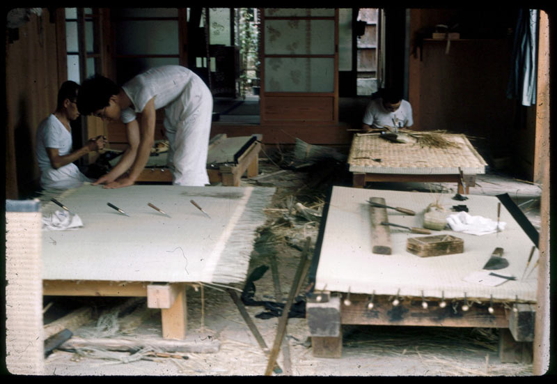 Three men crouch over their work stations in a small workshop, making white woven tatami mats in Japan, 1960.