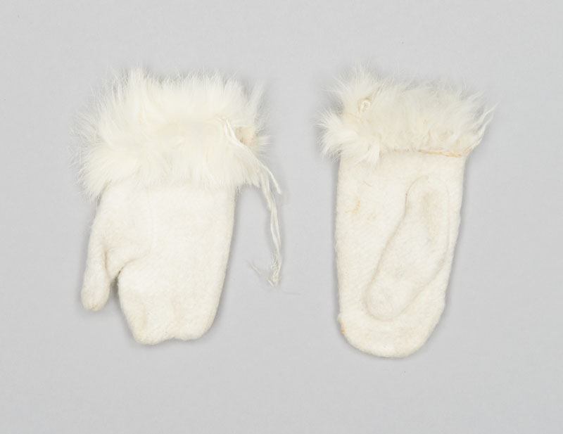 "Small white baby mittens made from thick, machine-knit wool, felted, and trimmed with white rabbit fur, a label reading ""Made in Canada"" is attached to the inside seam."