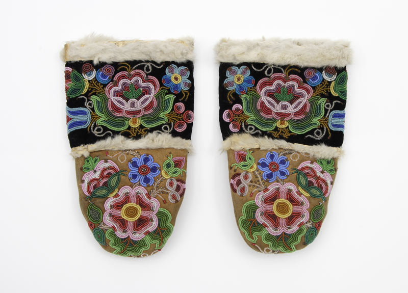 Two mittens made in the First Nations Dene tradition made from hide, velvet, and rabbit fur, and florally decorated with colourful glass and metal beads.