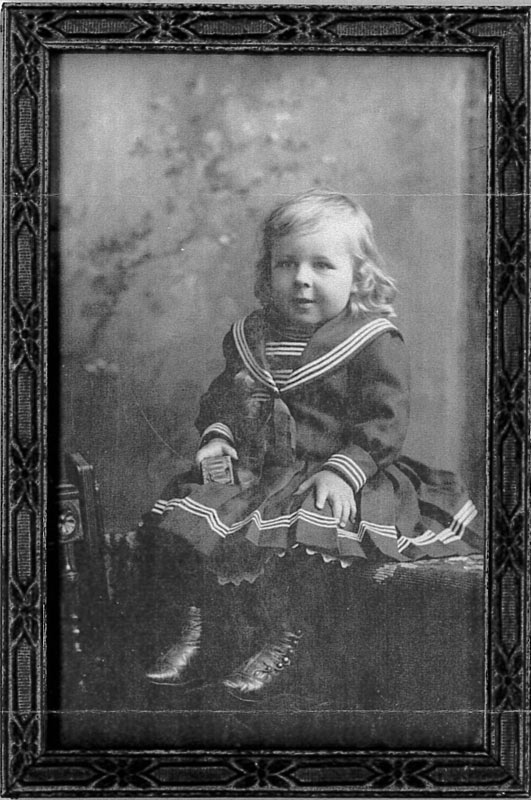 Black and white copy of a framed posed portrait of a young boy with long curly hair and large leather boots, wearing the sailor suit, circa 1900.