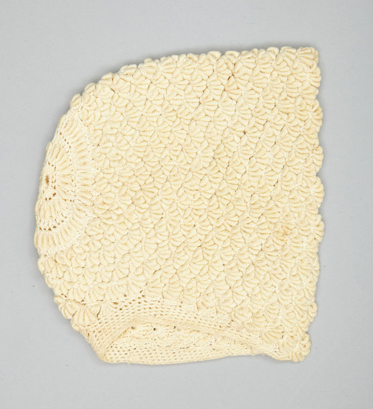 A white crocheted cotton bonnet skillfully handmade for a baby, made by Sonja Shelly in 1927 for her newborn daughter, Grace.