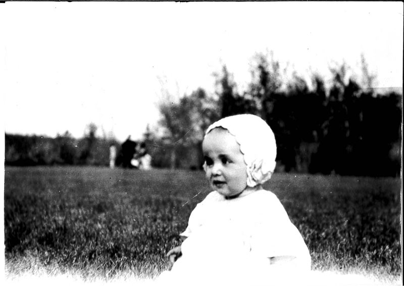 Photograph of a baby seated in a grassy field, Grace Shelly as a baby wearing the bonnet made by her mother, circa 1928 in Saskatoon.