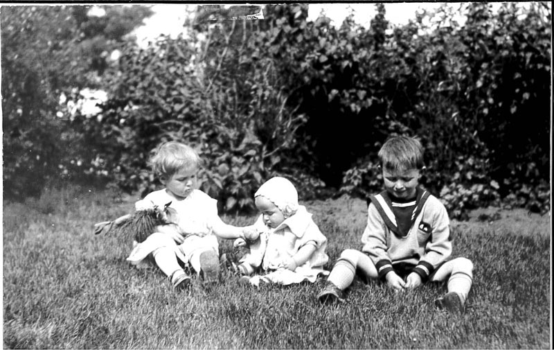 Three children in a candid portrait seated in a grassy field. Grace Shelly and siblings wearing a bonnet made by her mother circa 1928 in Saskatoon.
