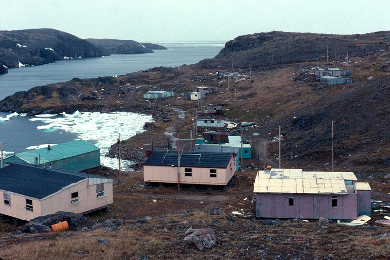 Photo of the abandoned town of Killiniq, Nunavut with a number of dilapidated homes surrounding a small icy bay.
