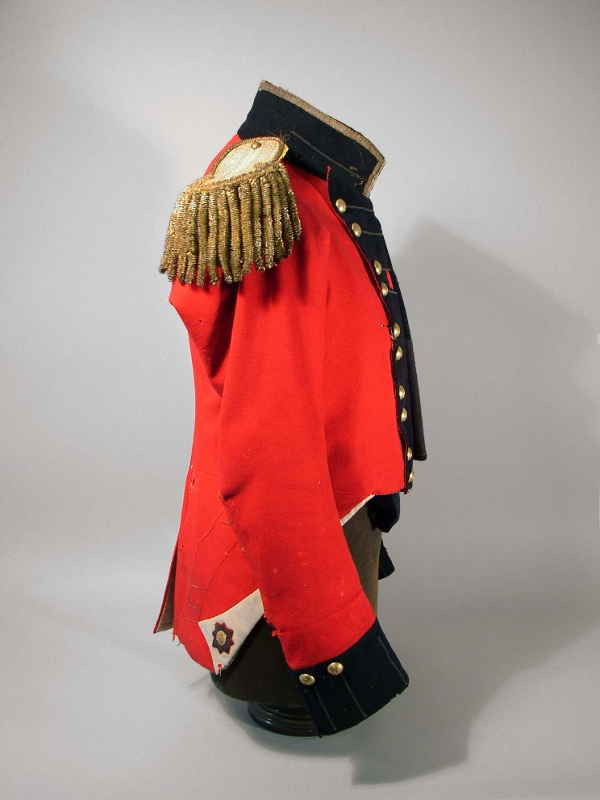 Side view of the scarlet military coat of Aeneas Shaw, showing tears but otherwise in good condition.