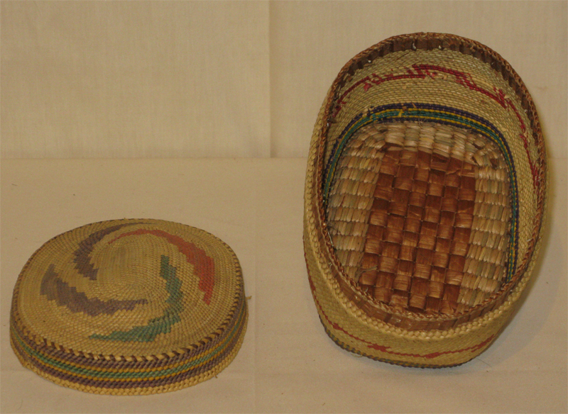 A squat oval, tightly woven cedar basket with bands of red, purple and blue dye running horizontally. A lid in the same style rests beside it.