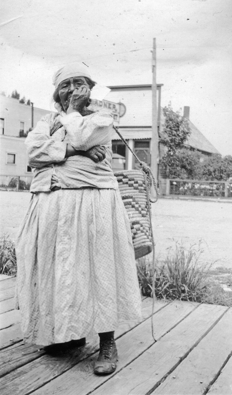 Elderly woman of the Tsawwassen First Nation carrying basket in the small town of Ladner, British Columbia.