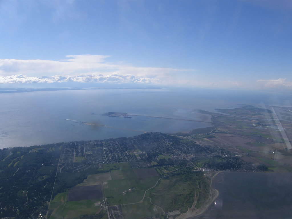 An aerial photo of modern Tsawwassen, British Columbia depicting water broken by a thin bridge of land.