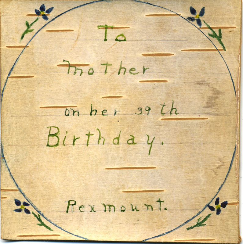 A round birch bark greeting card with child's writing in green saying 'to mother on her 39th birthday.'