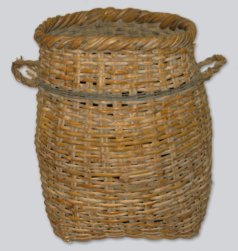 A woven deep rattan basket with two handles, brown and dusty with age but still sturdy. Made of a mix of Chinese rattan and local British Columbia reeds.