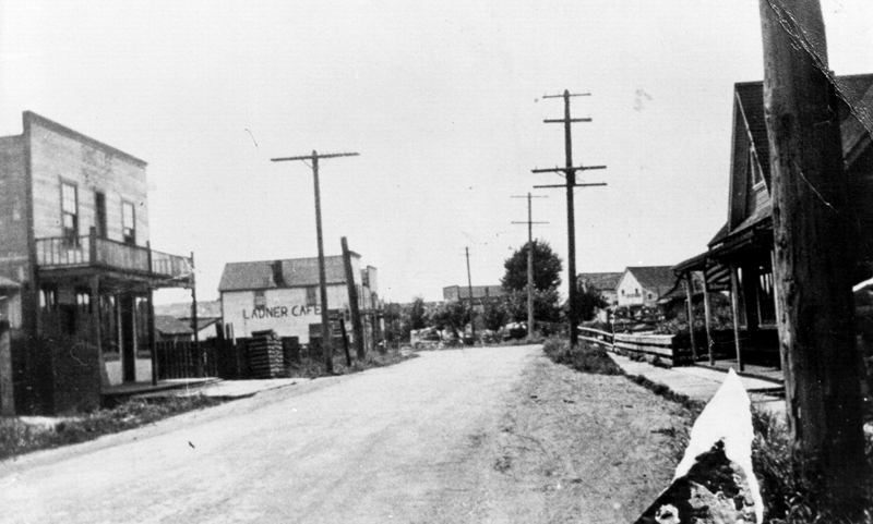 An early 20th century photograph of the Chinatown in Ladner, British Columbia. Wooden shops line a mud road.