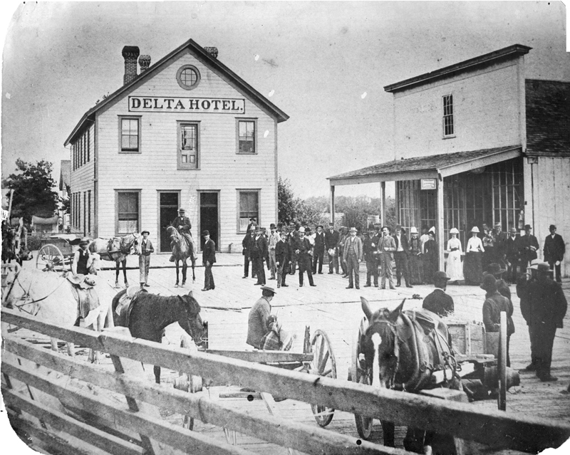 Historic photo of a crowd of men, women and horses assembled at wooden buildings in the rural town of Delta, British Columbia.