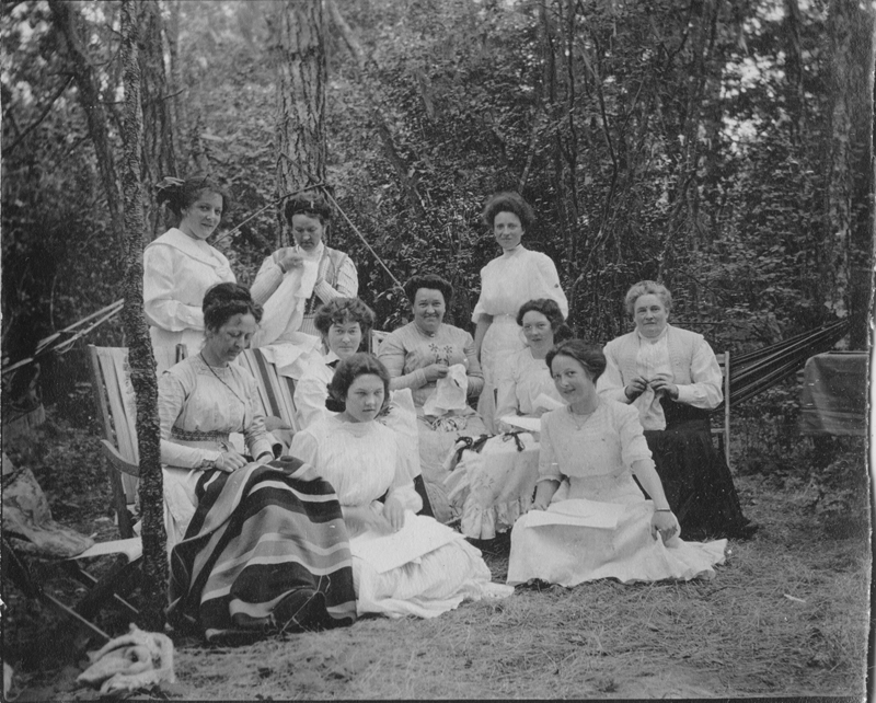 Ladies pose in early 20th century dress for a group photo while drinking tea and working on sewing projects.