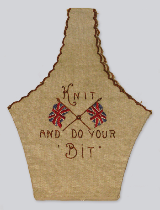 A World War One era bag made from wool stitched on muslin, embroidered with two crossed British flags and the words 'knit and do your bit.'