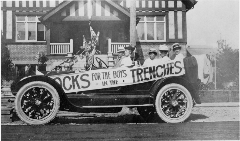 A World War One era car decorated with pro British slogans and flags encourages participation in the War effort.