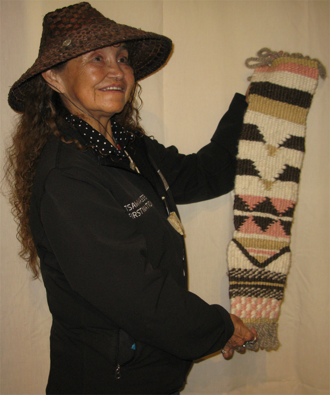 A woman in a traditionally woven cedar hat displays her weaving project which includes a flying geese pattern.