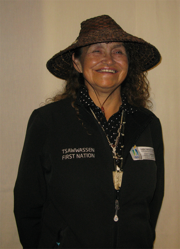 Posed portrait of Loretta Williams of the Tsawwassen First Nation wearing a cedar hat she created herself.