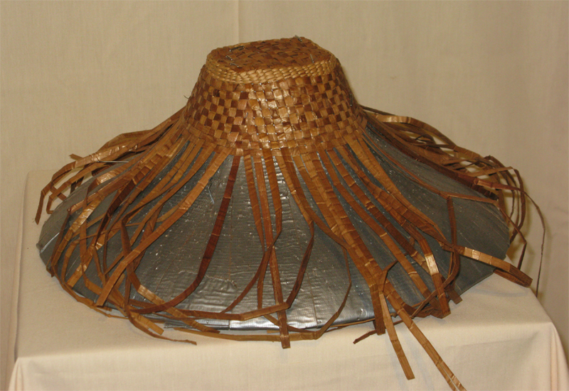 A partially completed woven cedar hat on a shaped base, the upper portion complete while the rest hangs loose.