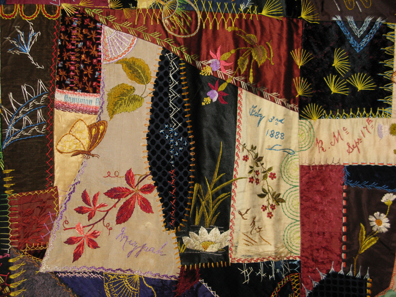 "A detailed view of the McKee crazy quilt showing the multitude of scraps, including the embroidered word ""Mizpah""."