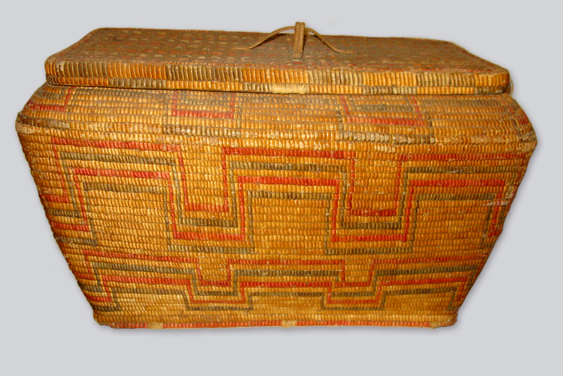 A basket in traditional Salish cedar weaving style, a rectangular hipped base with a narrowed top, decorated with interlocking red and green lines.
