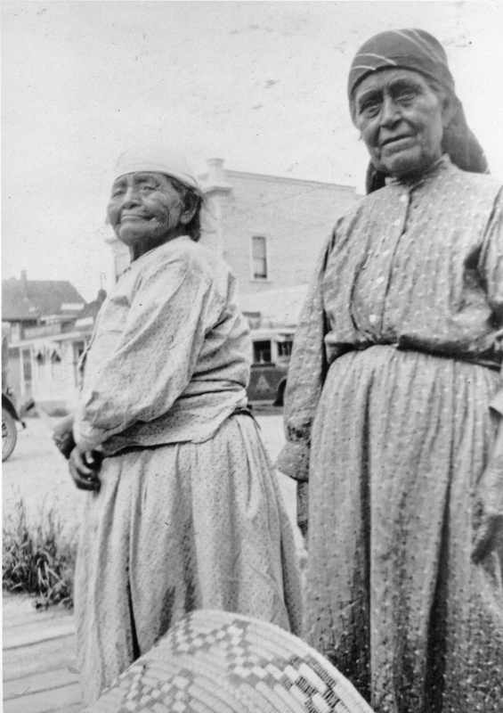Two women of the Tsawwassen Nation stand in the small town of Ladner, British Columbia, holding a similar basket.